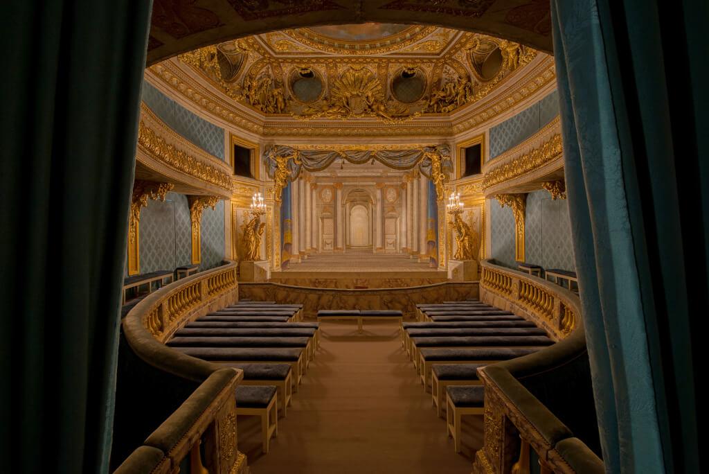 Intérieur du Petit Théâtre de la Reine: vue sur la salle avec lumière ambiante; en fond, décor de scène du Temple de Minerve, par les frères Slodtz (1754). © Château de Versailles / Thomas Garnier.